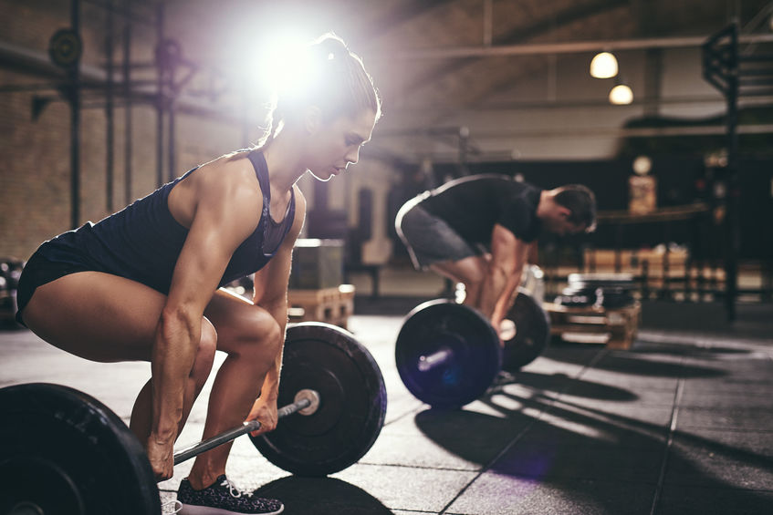 woman performing deadlifts one of 4 routine weight lifts you should be doing
